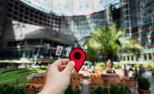 Unha persoa suxeita coa man un sinal típico de aplicacións de localización dentro dun edificio.