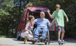 Un home en cadeira de rodas por unha lesión na medula espinal xunto á súa muller e o seu fillo.
