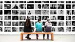 Tres mulleres de costas sentadas nun banco mirando fotografías nunha parede.