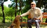 Un home cego sentado nun banco dun parque acariña ao seu can.