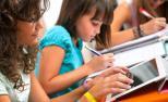 Unha nena con discapacidade auditiva segue a clase a través dunha tableta.
