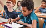 Un neno utiliza unha tableta de Microsoft e as ferramentas de aprendizaxe na escola.