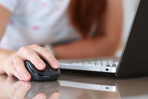 Moza movendo un rato diante dun portátil.