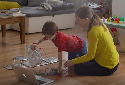 Una madre y su hijo realizan una actividad educativa tecnológica.
